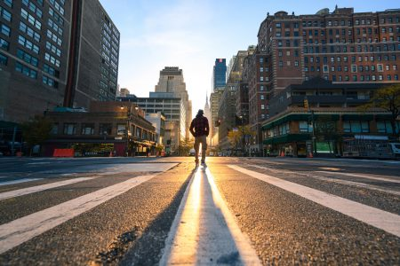 accenture One person crossing a junction in Manhattan at sunrise, New York City